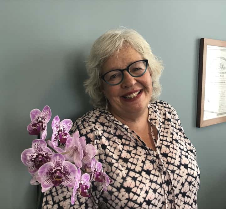 Judy Whisnant smiling standing with pink orchids