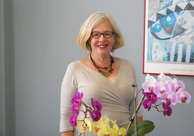 Judy Whisnant standing behind colorful flowers